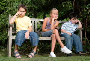 bored children sitting on a bench