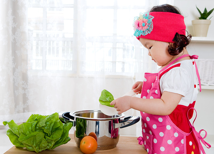 Young child having age-appropriate fun in the kitchen
