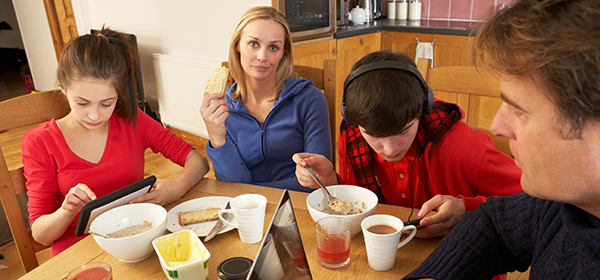Family eating breakfast and staring at phones & computers