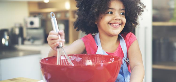 child stirring a red bowl