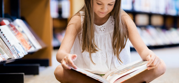 Child reading in library in the summer