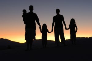 family silhouette standing in sunset